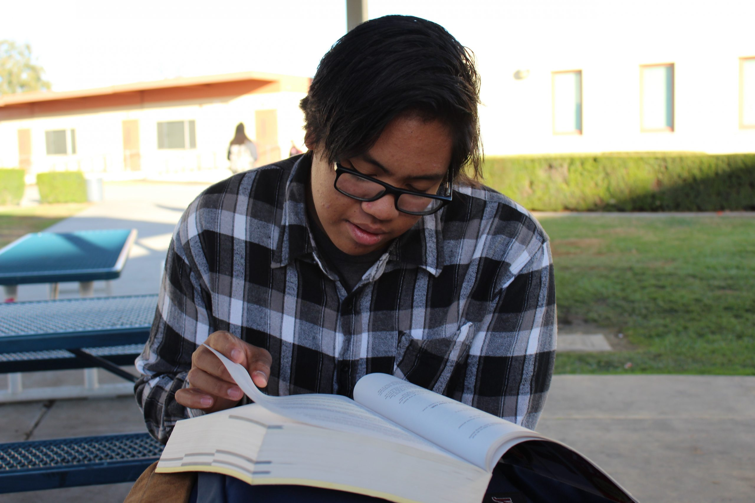 Male Filipino student reading a textbook outside