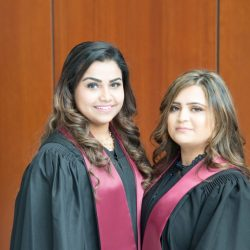 Two graduates looking into the camera