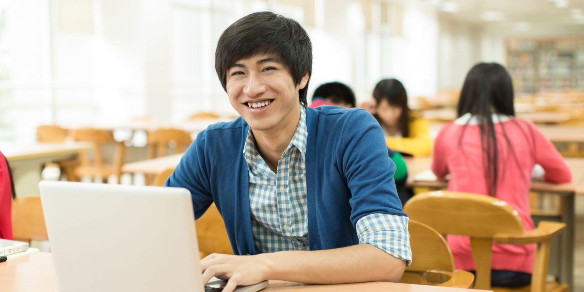 Asian college students studying with laptop in library